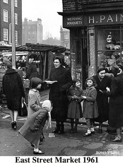 """East Street Market 1961. Salvation Army members and children outside a florists.  """"East Street is also the birthplace of Charlie Chaplin and features in the title sequence to the television programme Only Fools and Horses."""""""