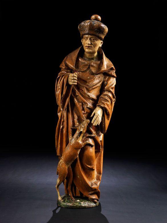 Geschnitzte und gefasste Standfigur, mit Resten der Originalfassung. Der Heilige, einer der Vierzehn Nothelfer und als Patron gegen Viehkrankheiten verehrt, im ...