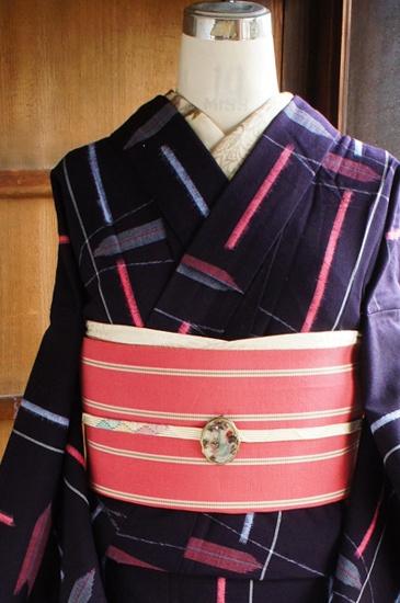 ほとんど黒に近い濃紺地に、ミストラベンダーブルーとピンクで織り出された矢羽とストライプの幾何学模様がレトロモダンなウールの単着物です。