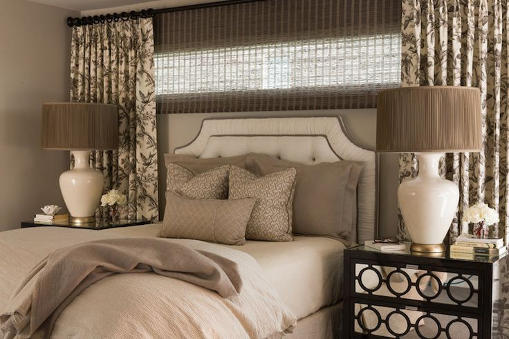 Nifelle Design - bedrooms - ivory and brown bedroom, bed under window, headboard under window, layered window treatments, ivory and black curtains, brown roller shade, ivory headboard, ivory tufted headboard, taupe bedding, mirrored nightstands, ava nightstand, ivory lamps, brown lamp shades,