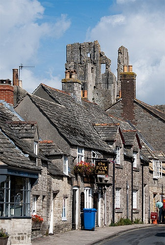 ~Corfe Castle is a fortification standing above the village of the same name on the Isle of Purbeck in the English county of Dorset.