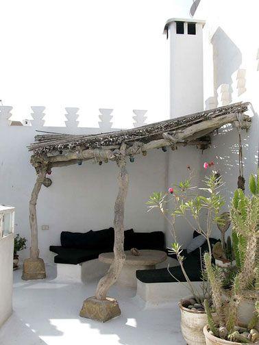 Une astuce déco pratique pour se protéger des rayons du soleil, aménagez un salon de jardin sous un auvent réalisé avec de la brande, des canisses et des rondins de bois