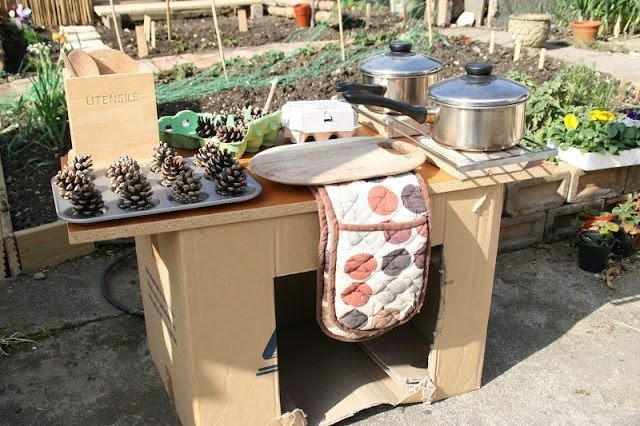 Simple outdoor kitchen made with a cardboard box & a piece of wood