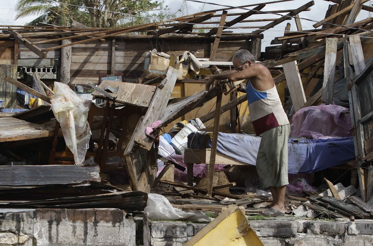 Resident Antonio Garces tries to recover his belongings from his house destroyed by Hurricane Sandy in Aguacate, Cuba, Thursday Oct. 25, 2012. Hurricane Sandy blasted across eastern Cuba on Thursday as a potent Category 2 storm and headed for the Bahamas after causing at least two deaths in the Caribbean.