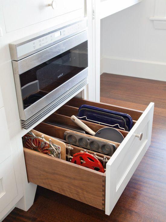 organize awkward dish ware in a drawer. cupcake pans, trivets, racks