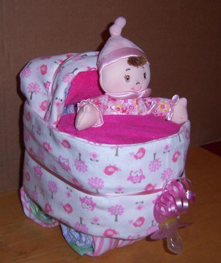 """1 Bassinet (Made with about 19 Diapers, 1 Gerber Receiving Blanket, 1 Gerber Cloth Diaper/Burp Cloth, 1 Laughing Doll (press her belly and she laughs), 1 Pacifier, and about 4 Wash Cloths) *(measures about 9""""x8""""x7"""")"""