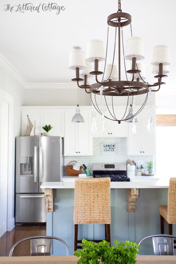 Open Plan Cottage Kitchen Features Wooden Dining Table Lined With Industrial Metal Chairs Illuminated By An Iron Chandelier Accented Crystal