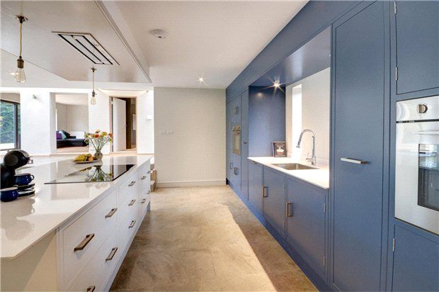 A grey-blue paired with the white units and worktop create a contemporary atmosphere in this Parlour Farm Kitchen