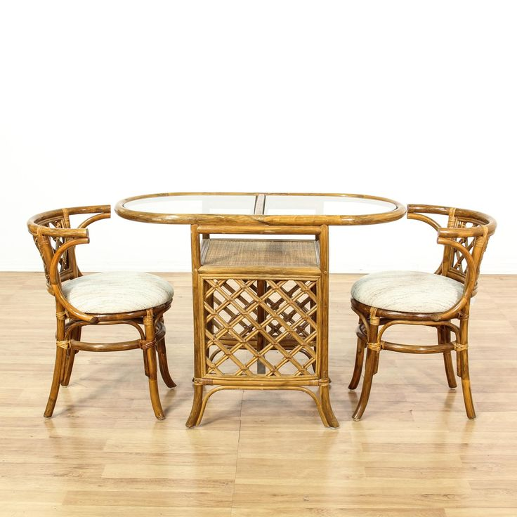 This tropical dining set is featured in a rattan with a glossy medium finish. This bohemian dining set has a curved glass top dining table with latticework panels and 2 dining chairs with curved backs and white woven upholstered seat cushions. Unique dining set perfect for a covered outdoor patio or sunroom!  #coastal #tables #diningset #sandiegovintage #vintagefurniture