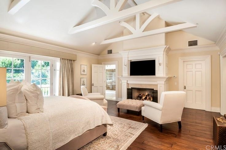 Traditional Master Bedroom with stone fireplace, Hardwood floors, Crown molding, Carpet, Cathedral ceiling