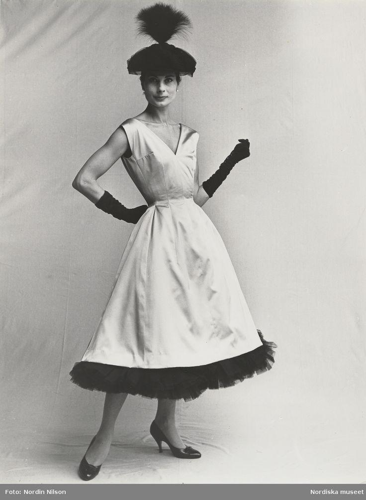 NK efter modell från Balenciaga, 1955. Modell i aftonklänning med svart tyllkant längst ned, svart hatt med fjäderplym, handskar och pumps. Fotograf: Nordin/Nilson