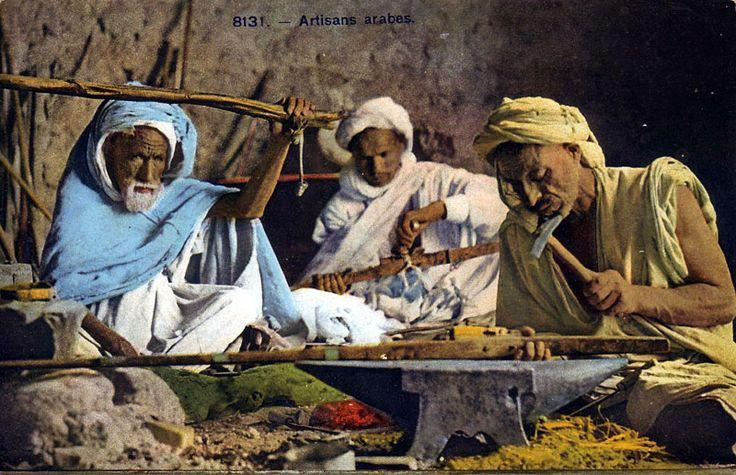 Armuriers au Maroc : Un beau moukahla en préparation pour les fêtes du baroud. Le vieil artisan de gauche a la main sur le bâton actionnant le soufflet de forge, et celui de droite semble clouter les éléments décoratifs de la crosse, avant de fixer la platine à silex.