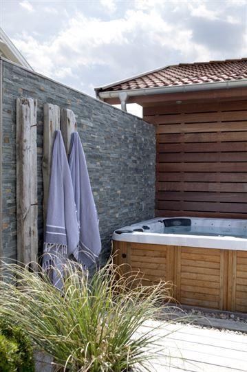 Spabadet kommer från Catalina spas och är inklätt i ädelträ. Fondvägg i skiffer från Flisby. Runt badet ligger nedsänkt trä från den gamla bryggan samt runda stenar som fin trampyta. På skifferväggen har 3 lodrätta trästockar placerats för dekoration och upphängning av handdukar.