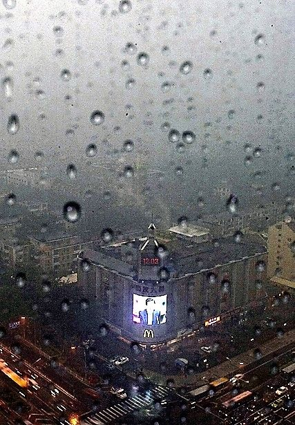 Rain drops covered a window of a building at Beijing's Central Business District while Chinese President Hu Jintao spoke on a screen during a thunderstorm
