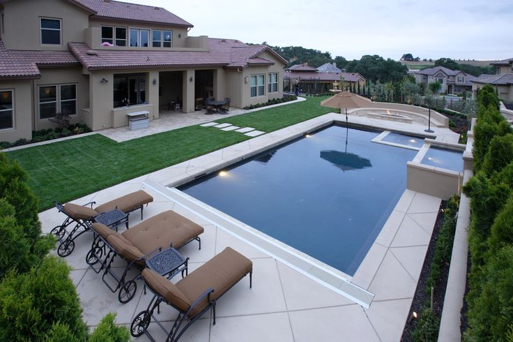 Suburban home with modern pool and hot tub as well as fire pit on one side.
