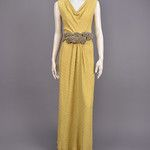 Bias-cut yellow silk with raised and puckered circles having silver metallic brocade, sleeveless bodice with draped neckline wrapping around twisted back above slit to waist,  wide self belt with silver baubles, trumpet flared skirt shirred below center waist. B-36, W-24, H-36, L-60. (Two small red marks-one on bodice back, one hidden in neckline, some metallic thread loss on baubles) good. GLC 500-700