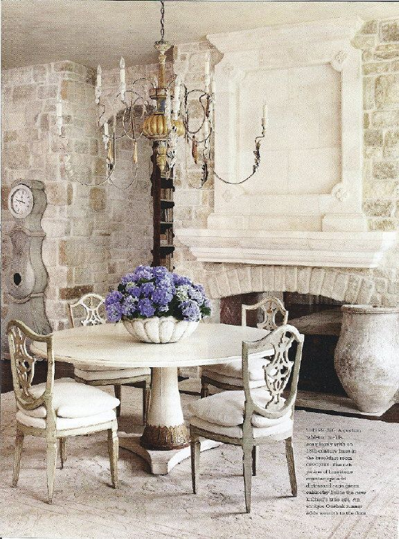 stone + open fireplace + chandelier - Dining room with a pop of blue flowers. Gorgeous!