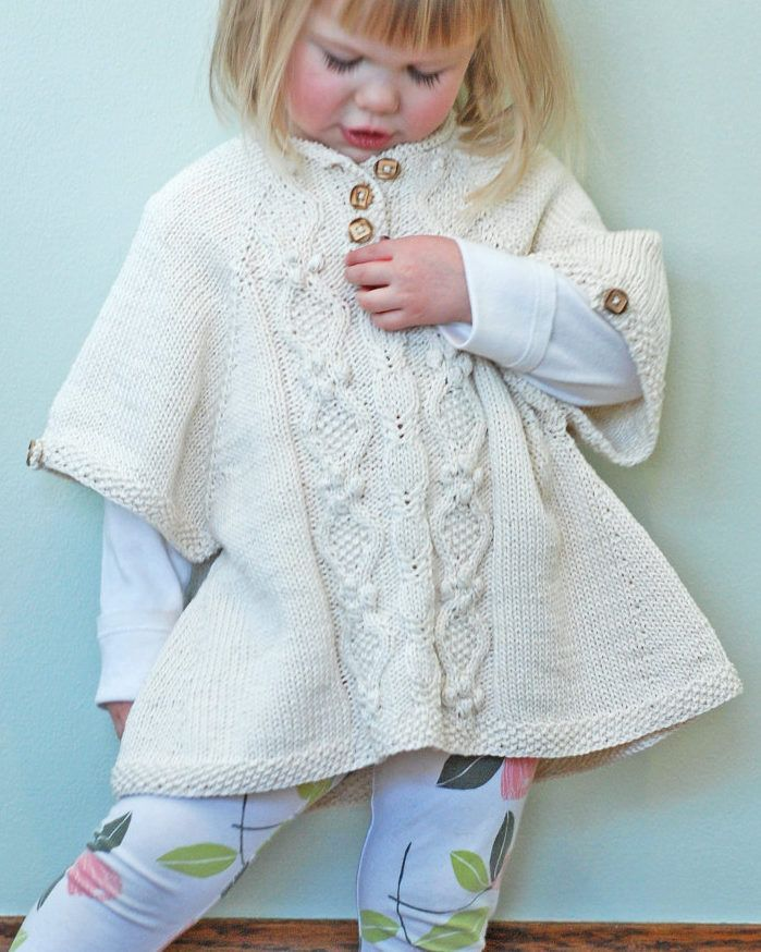 Knitting Pattern for Little Tourist Poncho - Tunic length, comfy, roomy, poncho with sleeves and cable panel. Baby and child sizes from 3 months to 10 years. Designed by Jenni Lansing