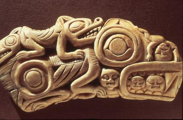 Intricately carved amulet with bear crest, bear cub, and humans.