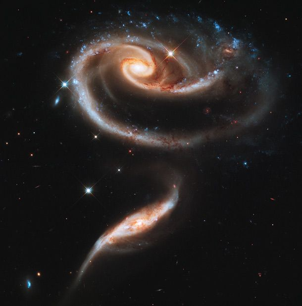 Two galaxies that passed close by each other and distorted each other's shape due to the intense gravitational attraction between them