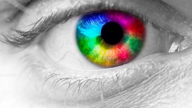 Das Foto zeigt ein menschliches Auge, in dessen Pupille die Farben des Farbkreises montiert wurden.
