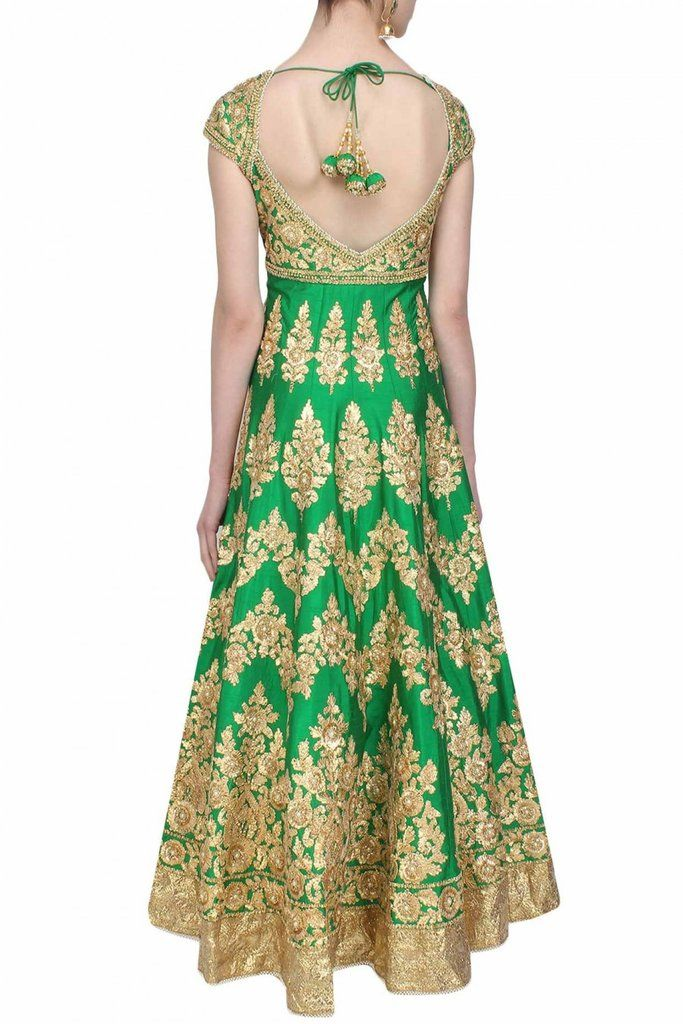 This green anarkali is made in raw silk base appliqued with floral pattern gold gota patti work and beads embroidered motifs all over the front and back ghera and yoke. This anarkali is embroidered wi