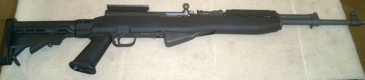 A sporterized SKS carbine fitted with an aftermarket composite stock and scope rail.