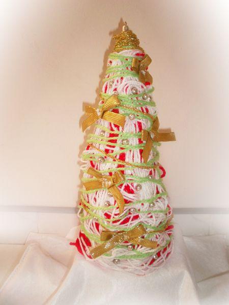 Árbol de navidad con lana, cinta dorada, cono de icopor y piedras.