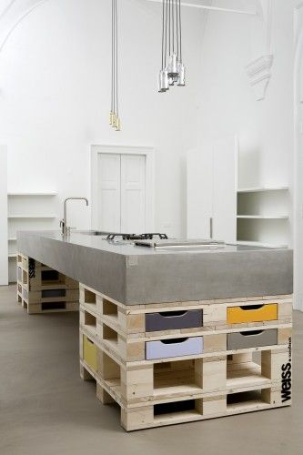 "weiss cucinebianchi officina milano fuorisalone 2012 01...Pallet Kitchen! Stacked pallets for poured & formed concrete countertop w/sink and cooktop...wonderful pops of color from custom-made ""drawers"" for spaces between stacked pallets...industrial/loft"