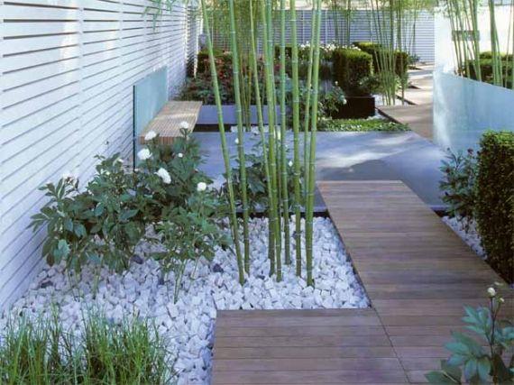 Pivoines blanches, tiges de bambou sur tapis de graviers blancs, buis taillés pour un jardin vert et blanc.