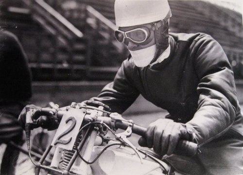 Motorcyclist. Padded leather one-piece suit. Gloves. Helmet with ear pads and chin strap. Goggles. Mouth mask. At a racetrack.