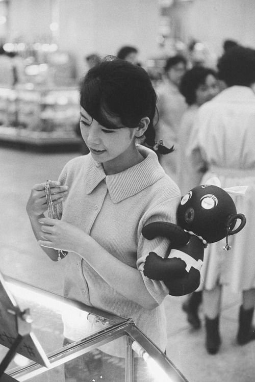 Japanese girl with a 'dakkochan' doll on her arm.   Tokyo, Japan, August 1960…