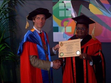 Rosetta Codling receiving his degree from Prof. Dr. William Martin, BIU CEO.