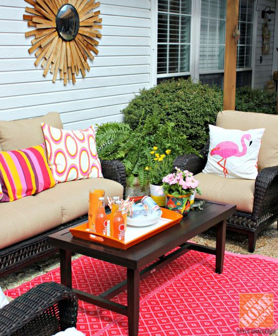 Patio Decor Ideas: DIY outdoor rug, dark wicker patio furniture and pink and orange pillows