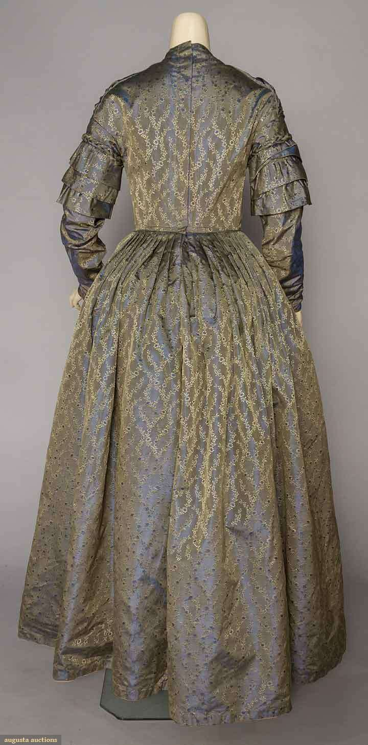 """BLUE & GREEN SILK AFTERNOON DRESS, c. 1845 Changeant blue-green ribbed silk w/ all-over small floral brocade, long boned V-front bodice lined in brown glazed cotton, knife pleated skirt lined in ivory glazed cotton, long sleeves w/ triple tierred caps & braided rouleau trim, B 34"""", W 27"""", L 56"""", (few light brown stains) excellent. MA Museum de-accession."""