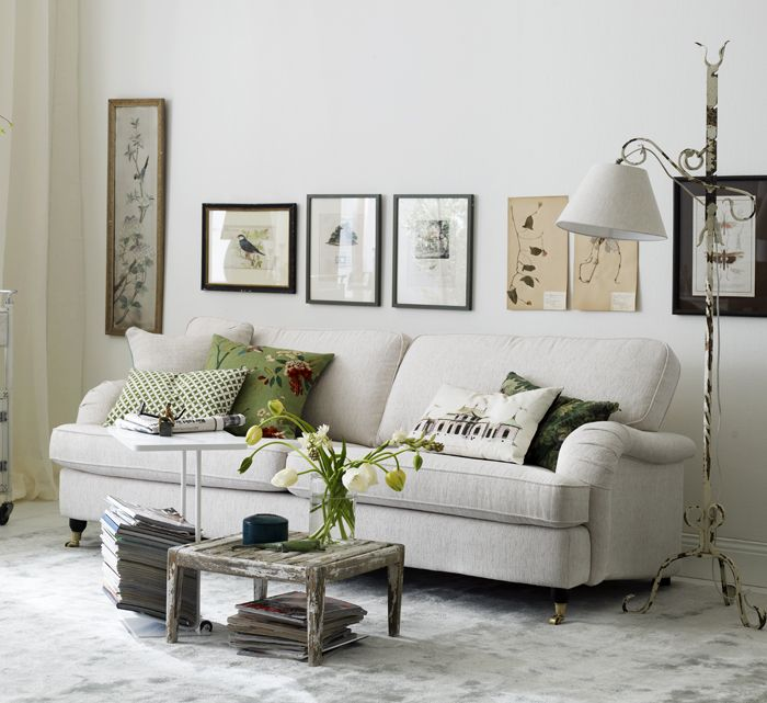 soft grey living room. love the row of art over the sofa.