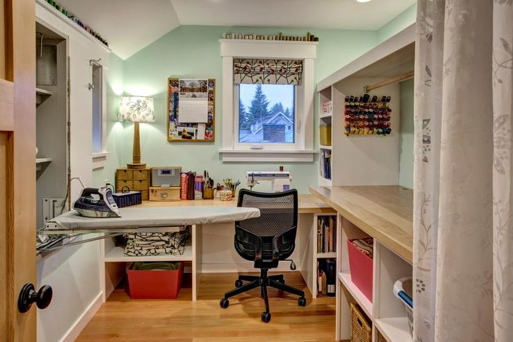Mint green walls add a soft but effective color to this cozy sewing room. Built-in shelving, thread storage and a folding ironing board keep the room organized and functional. Light wood countertops complement the hardwood flooring.