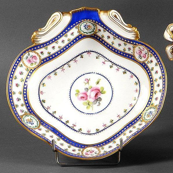 SEVRES Compotier coquille en porcelaine tendre, à décor central d'un bouquet de roses dans un cercle bordé de bleu et de pointillés or, lui-même inscrit dans un quadrilobe similairement bordé et orné d'une… - Coutau-Bégarie - 28/11/2012