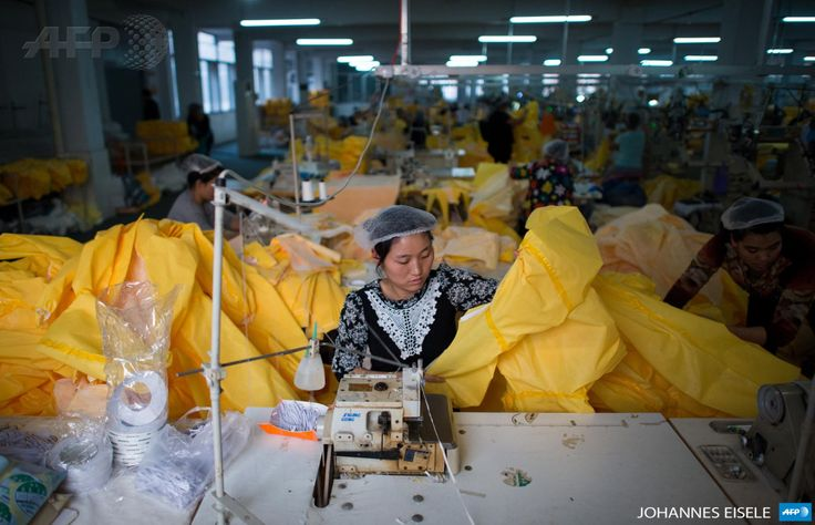 CHINA, Anqiu : This photo taken on October 23, 2014 in Anqiu, some 500 kilometers south of Bejing, shows women working on the CT1SL428, a protective suit for use in handling people infected with the Ebola virus, in a sewing room of Lakeland Industries Inc. Lakeland, a global manufacturer of industrial protective clothing, produces suits to be worm by healthcare workers and others being exposed to Ebola. AFP PHOTO / JOHANNES EISELE