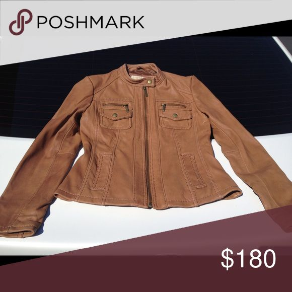 (NEW) Michael Kors Leather Jacket (NEW) Unworn. No tags. Size: XS. No holes or stains. New condition. Moto-style jacket. Soft leather. Nothing wrong with this. Does not fit me anymore. Color is a camel type color. Super cute. Michael Kors Jackets & Coats