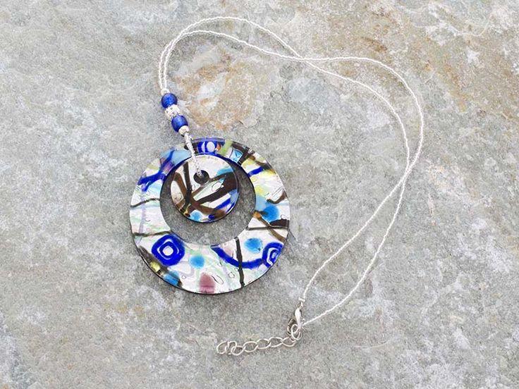 Pendente in vetro di Murano con doppia corona a forma di cerchio.   Base foglia d'argento, con splendide sfumature che vanno dal blu al verde.   La catena è fatta di perline in conteria, tutto in materiale anallergico (NICKE FREE).  Il cerchio è il simbolo dello spirito e dell'immaterialità dell'anima.