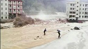 A phosphate factory worker stranded in rainstorm-triggered floods is rescued by his fellow workers in Deyang, southwest China