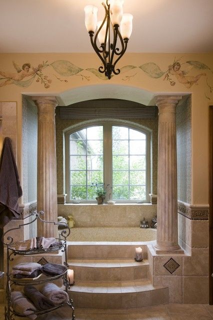 Beautiful Roman style bath, with an alcove tub framed by pillars, accessed  by marble