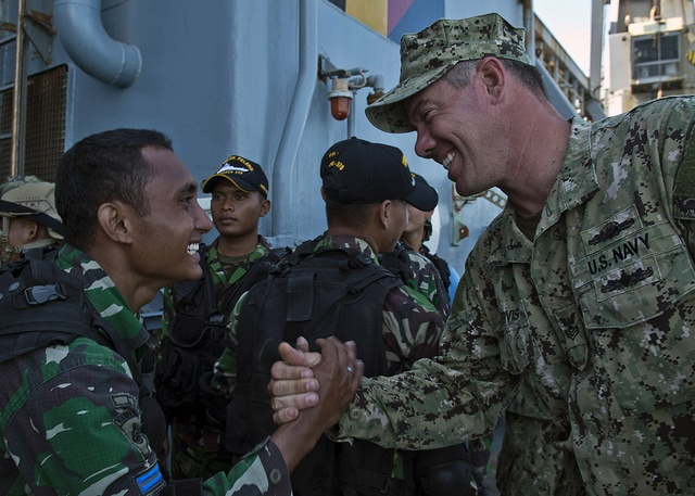 JAVA SEA (May 24, 2013) Electronics Technician 1st Class Anthony Nekervis, assigned to Maritime Civil Affairs and Security Training (MCAST) Command, shakes hands with a member of the Indonesian special forces boarding team Kopaska following a joint Visit, Board, Search, and Seizure (VBSS) training exercise aboard the forward-deployed amphibious dock landing ship USS Tortuga (LSD 46) as a part of CARAT 2013