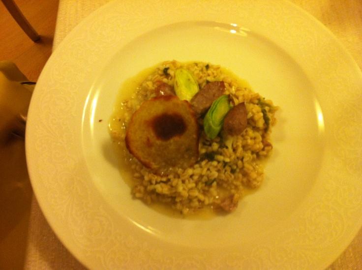 Orzetto mantecato con verza,  salciccia di Mora Romagnola  e porri brasati, cialda di patate.