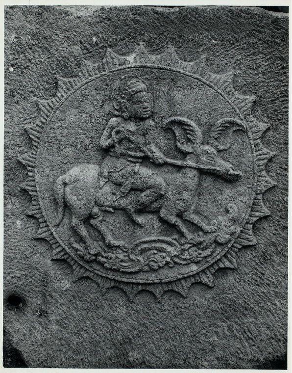 Java, East: Antiquities. Sawentar, candi. Surya mounted on stallion with wing-shaped ears. Relief on the keystone of vault from Tjandi Sawentar, Kediri, East Java, Vishnuite, early 14th century. Photo: D.P. 6879, list #113.