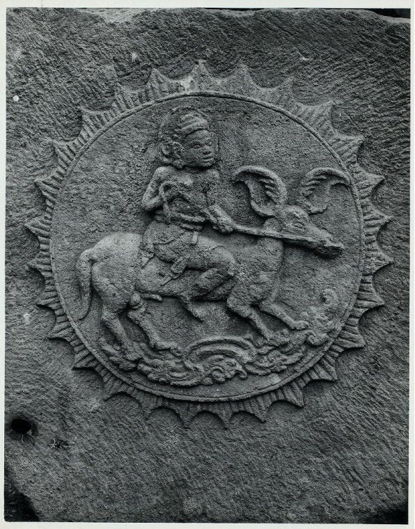 Java, East: Antiquities. Sawentar, candi. Surya mounted on stallion with wing-shaped ears. Relief on the keystone of vault from Tjandi Sawentar, Kediri, East Java, Vishnuite, early 14th century. Photo: D.P. 6879, list #113.