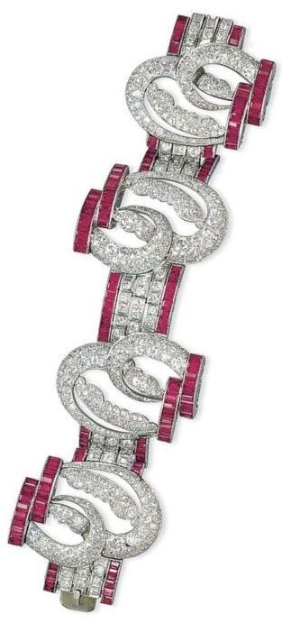 AN ART DECO SYNTHETIC RUBY AND DIAMOND BRACELET. Composed of four openwork pavé-set panels of double-arch design linked with diamond-set three-line spacers, to the synthetic ruby line borders, 1930s, 18.2 cm, with Austrian assay mark for platinum. #ArtDeco #bracelet