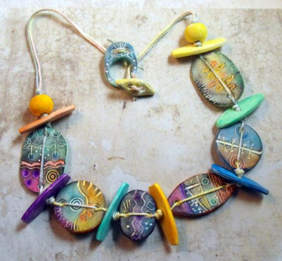This colorful necklace features textured polymer clay beads in different shapes. Each bead shows another pattern. All beads are tinted with chalks