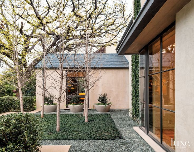 Floor-to-ceiling windows bring to light an architect's modern approach to traditional forms in this stunning courtyard-style Dallas residence.